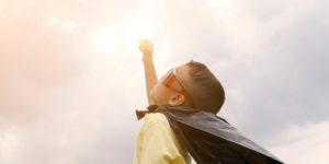 little boy in a cape with sunglasses reaching up to sun